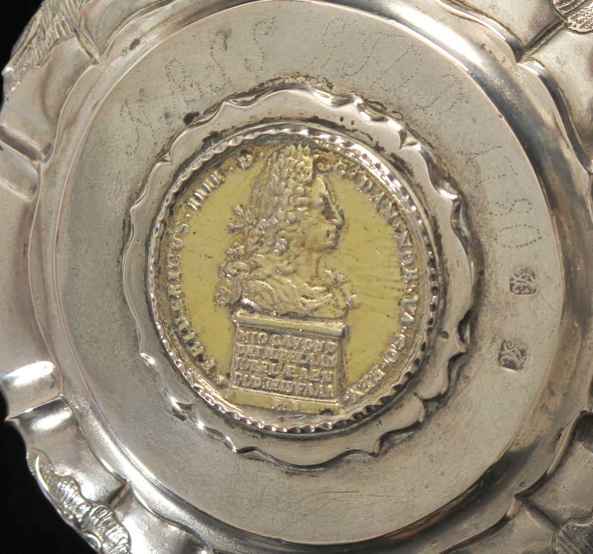 Stentøykrus m. lokk, 1780  sølv, rokokko,    Buet kant m. rette knekk, i annenhvert mellomrum  drevet og siselert rokokkokartusj, opphøyet lokkflate  m. mynt i sirkelrund innfatning m. profilert omriss,  havhest som lokknapp, rundt mynten, F4`s minnemynt om reformasjonen (AAM 2312), Eierinitialer innprikket i lokket, utydelig stempel på undersiden.   Lokket montert på stentøykrus,  brunt, rillet nederst, derpå glatt felt,  så lyst rillet feldt., buet, profilert hank.   Tilst juni 1961: God.