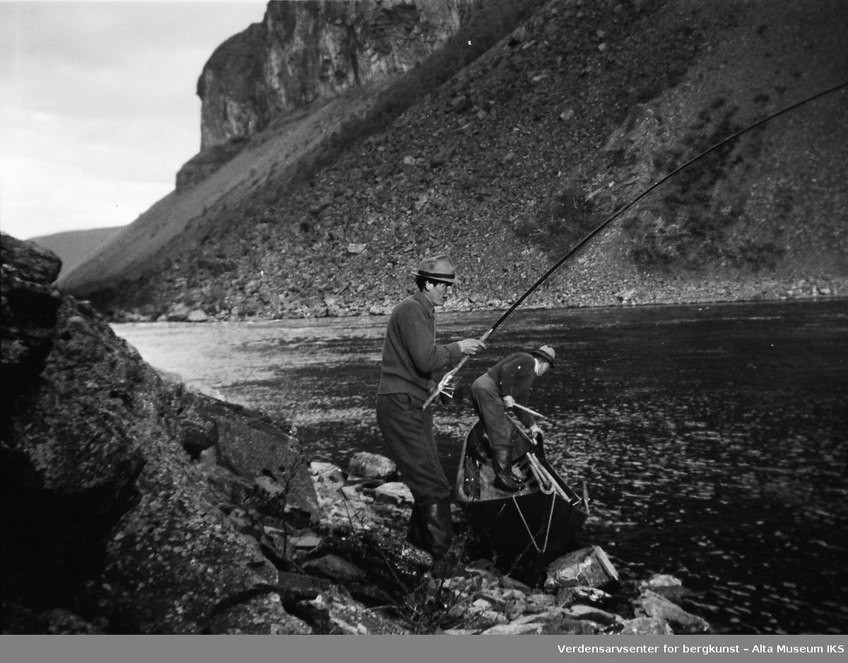 Paul Tangen fisker i elva, og en mann står i elvebåten.Bildet er tatt i fiskesesongen på sommeren i 1949.
