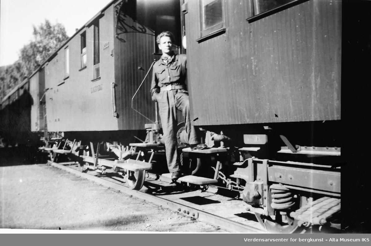 En ung mann står på et tog og ser utover. Bildet er tatt i 1945