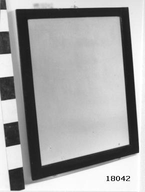 Rektangulär spegel med slät träram av betsad och fernissad mahogny, ramens B = 50 mm. Baksida klädd med kartong. Plattor för fastskruvning mot skott.