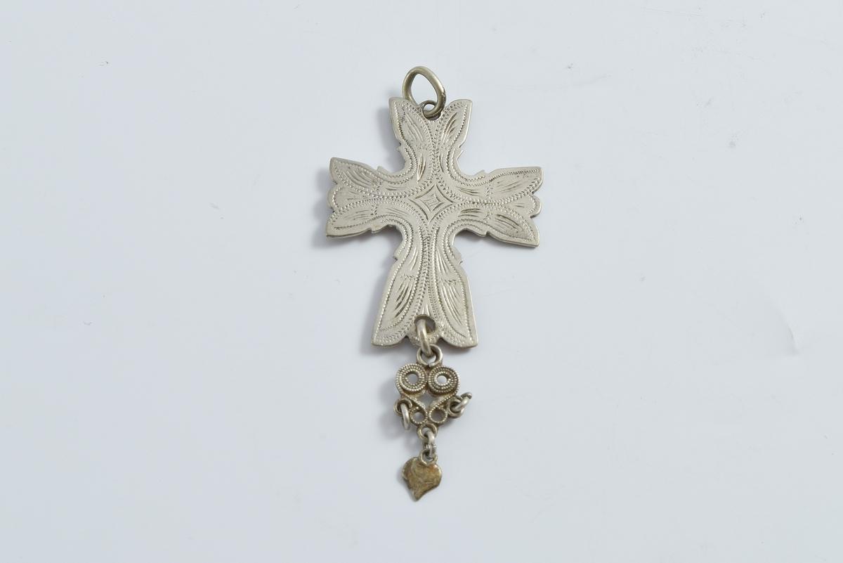 Korsformet anheng i sølv. Anhenget er gravert med bladlignende ornamenter. På undersiden av korset er det festet en filigransdobbe med hjerteformet løv.