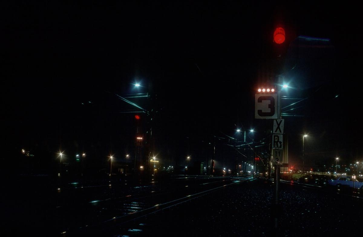 Hovedsignaler og høye skiftesignaler på Trondheim stasjon om kvelden. Hovedsignalene i forgrunnen er utkjørhovedsignaler, og i bakgrunnen skimtes brusignalet for Nidelv bru.