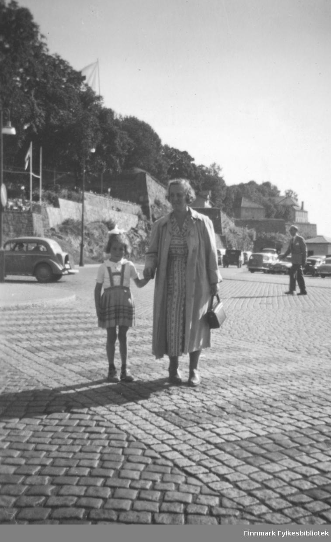 Torill Ebeltoft på ferie i Oslo i 1955. Her leier hun sin grandtante Lillemor. I bakgrunnen ser vi Akershus festning