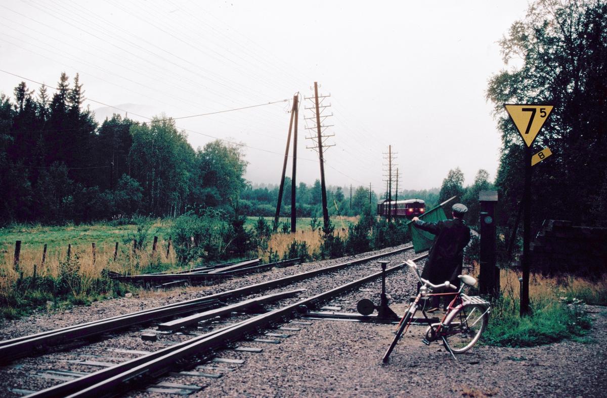 Togekspeditøren på Barkald stasjon setter opp innkjørsignal for tog 372 (Røros - Hamar).