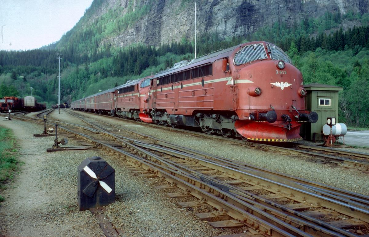 """Sørgående dagtog på Nordlandsbanen, tog 452, på Grong stasjon med NSB dieselelektriske lokomotiver type Di 3. I bakgrunnen kjører kryssende godstog ut. I forgrunnen mekanisk signal for dobbel kryssporveksel (""""Engelskmann""""). Ved siden av lok'et er bu med signalstillere for innkjøring fra Namsosbanene og fra Formofoss. Stasjonen hadde enkelt sikringsanlegg, dvs. Innkjørhovedsignaler med forsignaler og håndstilte kontrollåste sporveksler."""