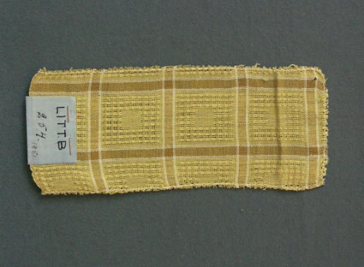 Prov till gardin vävd i tuskaft och stramaljbindning. Provet har bomullsgarn i varp och inslag.Ytterligare prov och vissa vävuppgifter finns i pärm gardiner A, litt B 254.