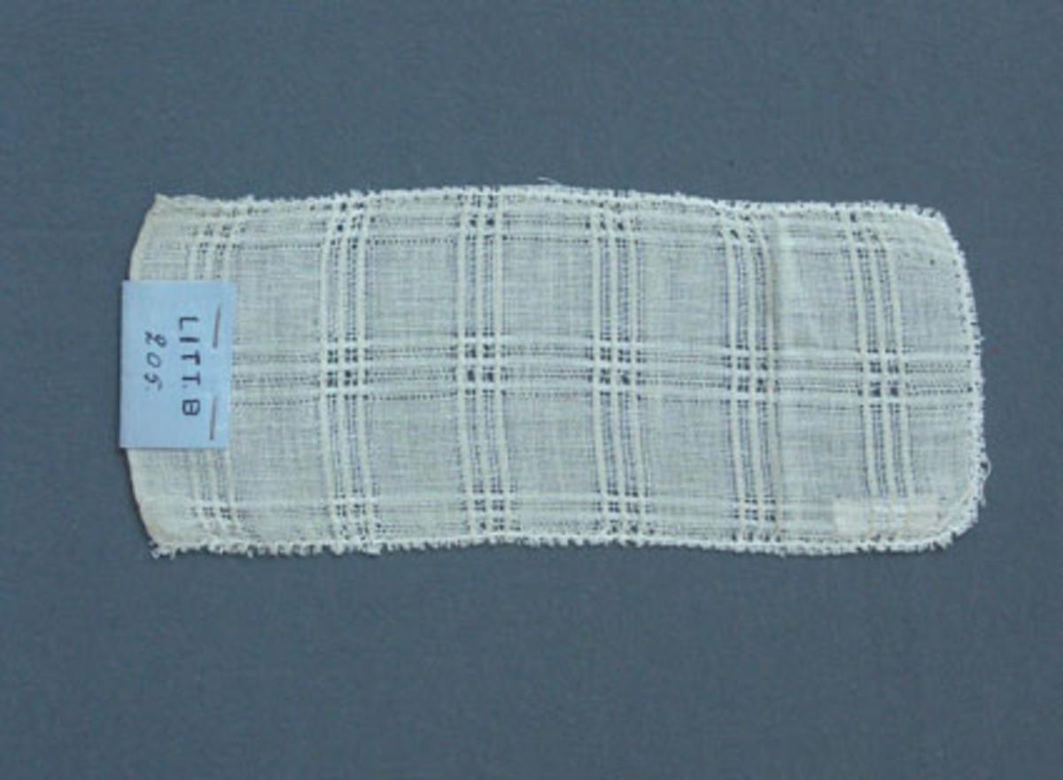 Prov till gardin vävd i tuskaft och stramaljbindning med bomullsgarn i varp och inslag.Ytterligare prov och vissa vävuppgifter finns i pärm gardiner A, litt B 205.