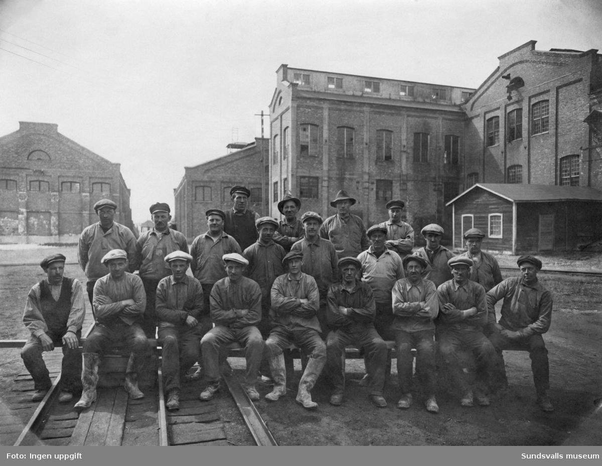 """Gruppfoto med arbetare vid Fagerviksfabriken. """"Fällmanslaget"""". Namnuppgifter finns på delar av arbetslaget."""