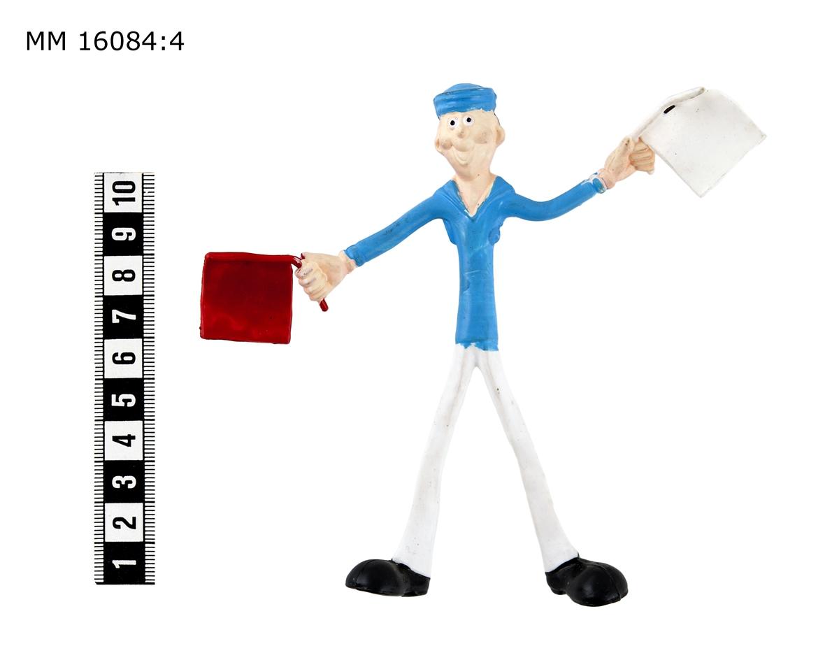 Figur i form av signalmatros, böjbar till olika ställningar. Signalmatrosen klädd i vita byxor, svarta skor, ljusblå bussarong och ljusblå rundmössa. Håller en röd semaforflagga i höger hand och en vit i vänster hand. Övriga kroppsdelar hudfärgade. Märkt på rygg och bakben: CO NB R 969409.