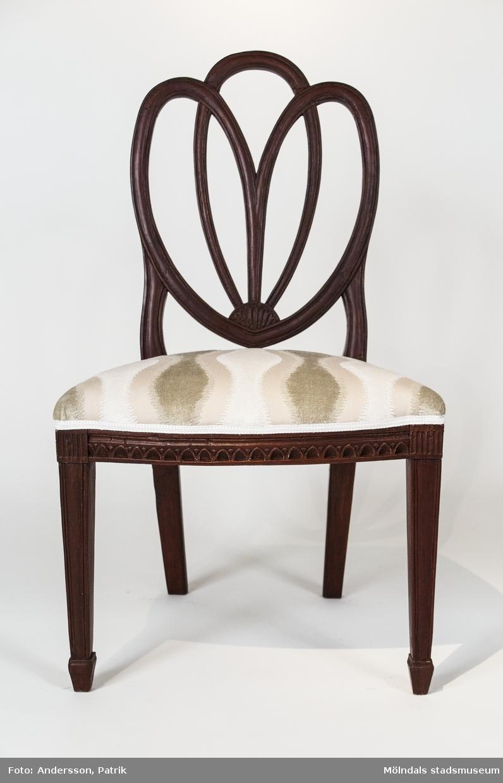 """Stol, brunmålad, tillverkad av björk. Hjärtformad rygg sammansatt av tre öppna bågar, Fyrsidiga nedåtavsmalnande ben som vid foten har en ansvällning.  Stolen ansluter nära till en förlaga av den engelske formgivaren George Hepplewhite (c. 1727-1788). Liksom förlagan har denna stol fotavslutningar som i Storbrittanien kallas för """"spade toe""""  och som kan översättas med spadtå eftersom de liknar en spade till formen.  Stolen är tillverkad i Lindome omkring 1800 och brännstämplad på baksargens insida """"SAS"""". Denna signatur har inte kunnat bindas till någon enskild stolmakare i Lindome.  Stolen äri inköpt på auktion 2007 och var vid förvärvstillfället målad i en ljusgrön färg, troligen från 1980-talet. 2013 lät museet en konservator ta fram och retuschera den brunröda originalfärgen. Det är vanligt att stolar från tiden omkring år 1800 har en brunröd originalfärg som ursprungligen varit ämnad att imitera det dyrbara träslaget mahogny. Sitsen är omstoppad och omklädd 2013."""