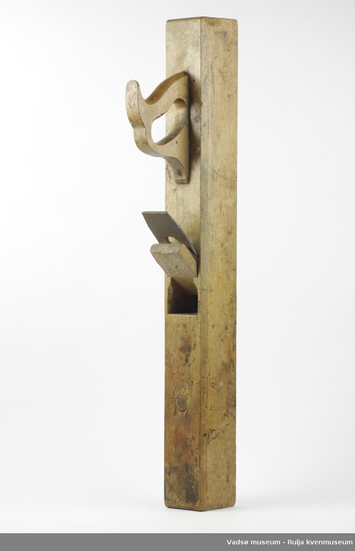 Langhøvel bestående av stokk, trekile og høveljern, samt jernelement mellom trekile og høveljern.  Stokken har flat glideside. Håndtaket er kilt og skrudd fast.