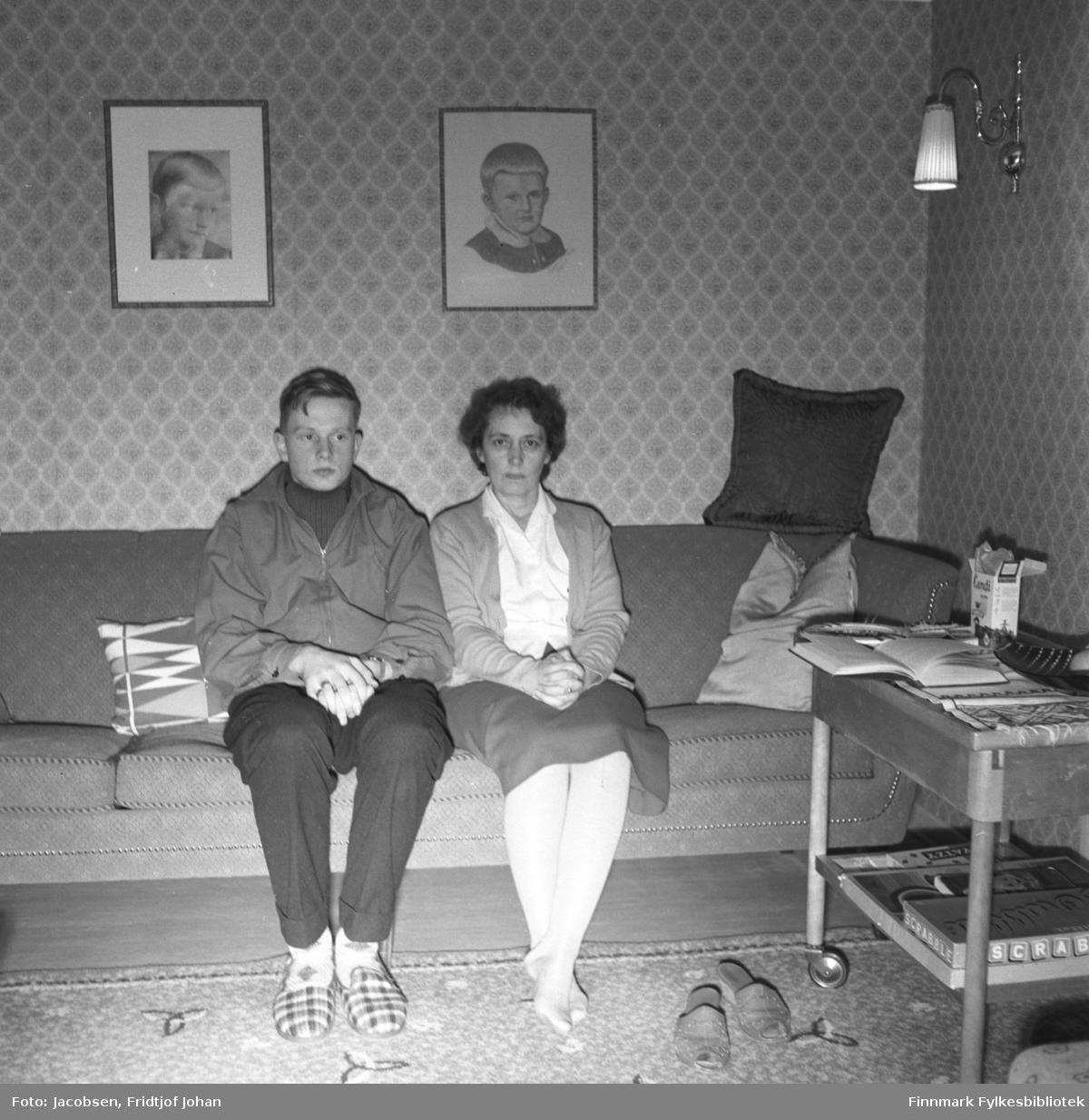 Arne Jacobsen og hans mor Aase poserer for fotografen i familiens hjem i Storvannsveien. Arne har mørk bukse, genser og litt lysere jakke på seg. På føttene har han rutete tøfler. Aase har et mørkt skjørt, lys bluse og en tynn jakke på seg. Sofaen de sitter i er forholdsvis mørk og flere sofaputer ligger i den. To bilder henger på veggen bak personene og en lampe henger til høyre på bildet. Et gulvteppe ligger på gulvet foran dem til høyre står  et bord med noen spill og andre ting oppå. Tapetet er mønstret.