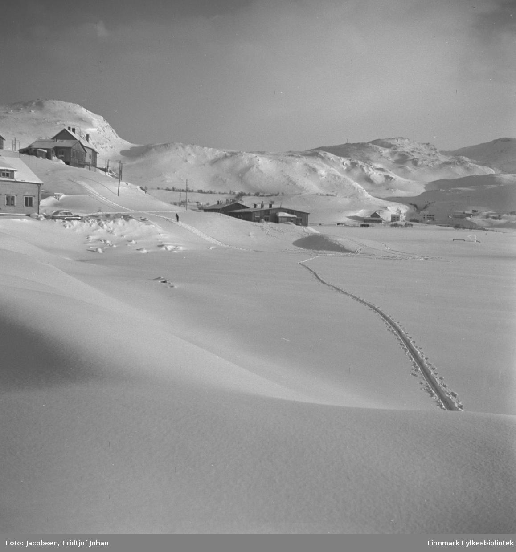 Bilde fra Storvannsveien i Hammerfest. Storvannet ligger is- og snølagt, bildet er tatt i retning mot kraftstasjonen. Bygget lengst til høyre er kraftstasjonen, til venstre for denne ligger Einangården med fjøs og jorde. Til venstre på toppen står en brakke og nyhuset til Roy Pedersen. En person går på ski opp mot huset.