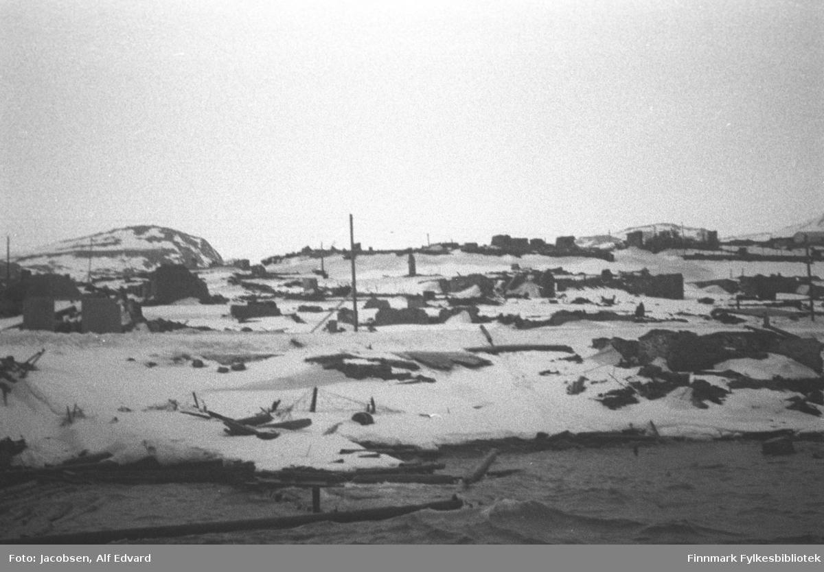Del av Hammerfest sentrum, i ruiner etter tyskernes brenning. Bare grunnmurer står igjen sammen med rester av bygningsmaterialer. Noen el-stolper står oppreist, spredt rundt på området som er avbildet. Rester av en kai ses midt på bildet der bare noen stolper stikker opp av sjøen. Det ligger en del snø i terrenget og litt bølger på sjøen. Øverst på bildet er området Moreneveien/Storelva. Fjelltoppen i bakgrunnen kan være fjellet rett ovenfor Sætergamdalen. Det har også noe snø på, men mange bare flekker også.