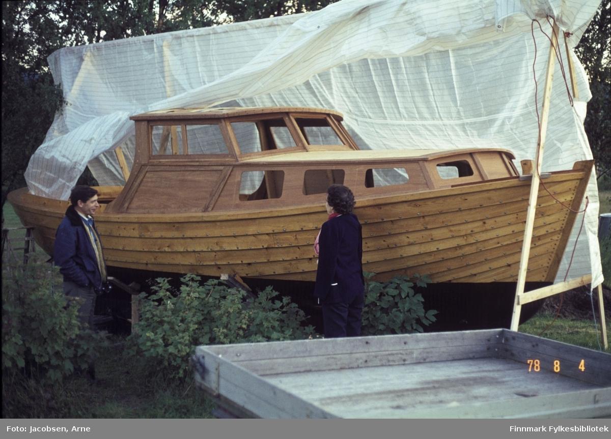 Aase Jacobsen og Øystein Nakken foran tresnekka hans. Båten ser helt ny ut, står på land og er delvis dekket av presenning så den klargjøres nok for sjøsetting. Mye høye trær skimtes i bakgrunnen og busker står i forkant av bildet. En tilhenger med trekarmer står nederst på bildet. Aase er kledd i mørke, lette klær og Øystein har olabukse og en mørk jakke med foret krave.