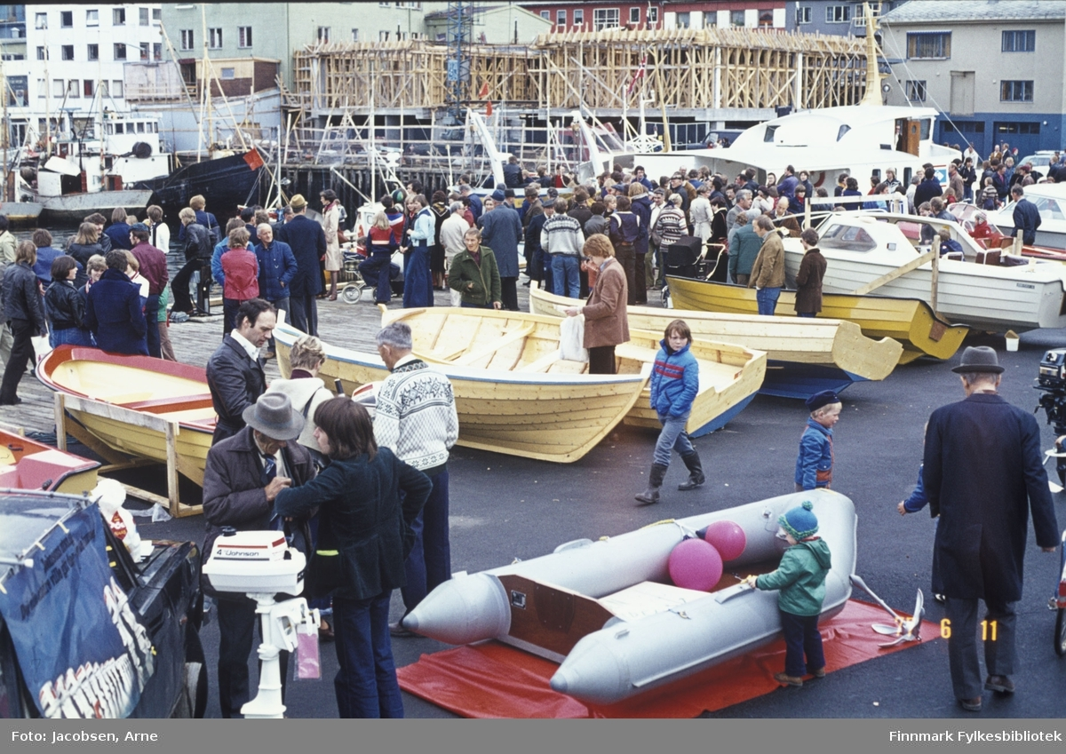 Båtmesse/salgsutstilling på Rådhusplassen/Rådhuskaia. Mye folk, både barn og voksne, har møtt opp og mange åpne småbåter er utstilt, samt to med overbygg. Det er både tre- og plastbåter. Innerst i havna, oppe til høyre i bildet, ligger FFR-båten M/S Vargøy og bygget under oppføring er Domus. Noen fiskefartøy ses også ved kai oppe til venstre. En gummibåt helt foran og 2 påhengsmotorer ses også. En dregg ligger ved siden av gummibåten og to blåser ligger oppi båten.