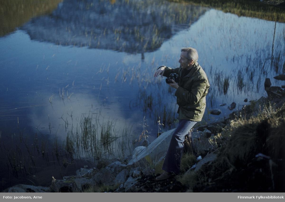 En mann på tur med fotoapparat. Han har olabukse og feltjakke på seg. Han står på bredden ved en vann. Det vokser litt siv i vannet langs bredden. Stein ligger i vannkanten og på land der han står. Vannet ligger blikkstille og et fjell, sannsynligvis Tyven, speiler seg i overflaten. Mangel på snøflekker i fjellet samt påkledningen hans tyder på en sen sommerdag/tidlig høstdag.