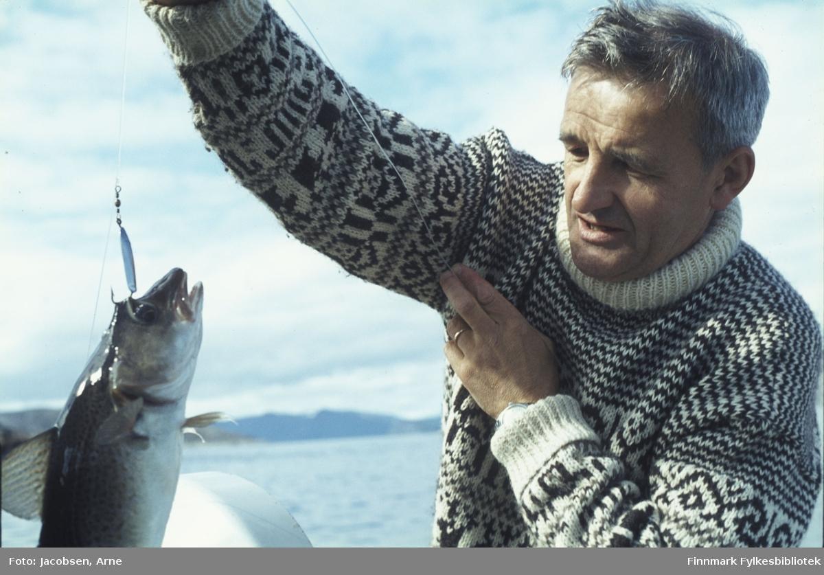 Mann, iført mønstret strikkegenser haler opp en torsk, sannsynligvis fra en småbåt fordi toppen av en påhengsmotor vises nederst i bilde. Fisken har ikke bitt på, men er blitt krøket. Hele sluken vises på bildet. Sola skinner og på det litt diffuse landskapet i bakgrunnen ses ikke noe snø så det er nok godt utpå sommeren