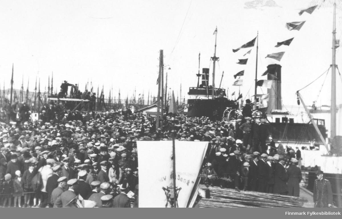 Fotografi fra dampskipskaia i Vadsø. Tatt i forbindelse med Vadsø bys 100-årsjubileum i 1933. Båtene er flaggpyntet. Det ble holdt et to dagers sangerstevne i byen. På bildet kan vi se flere sangere og hornmusikere. Det var møtt opp mange andre publikumere. Henviser til bilder nr. 98012-123 0g 98012-124 for flere opplysninger