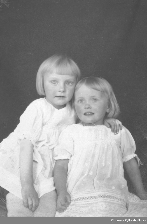 Portrett av Gerd og Liv Vibe Jacobsen fra Bergen. De er døtre av August Magnus Jacobsen fra Vardø og hustru Solveig Johannessen Jacobsen fra Bergen. Gerd som holder armen sin rundt søsterens skulder er kledt i en hvit lang skjorte. Liv har på seg en hvit kjole