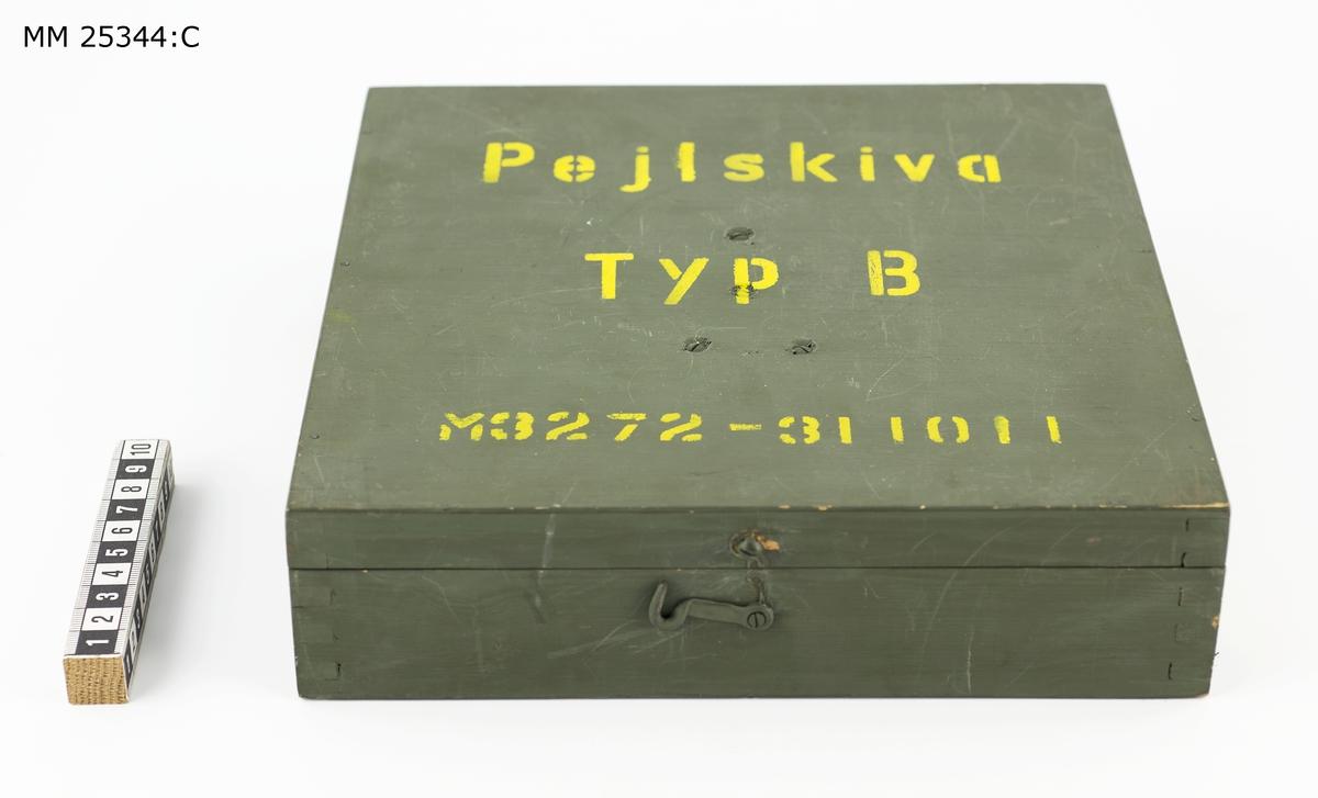 """Grön låda i trä med öppningsbart lock som sitter med två gångjärn på baksidan. Text på locket: """"Pejlskiva TYP B M3272-311011"""". Lådans lock kan låsas med en hasp på framsidan. På insidan finns trälister fastsatta för mintering av pejlskivan och siktet, som hängs i locket."""
