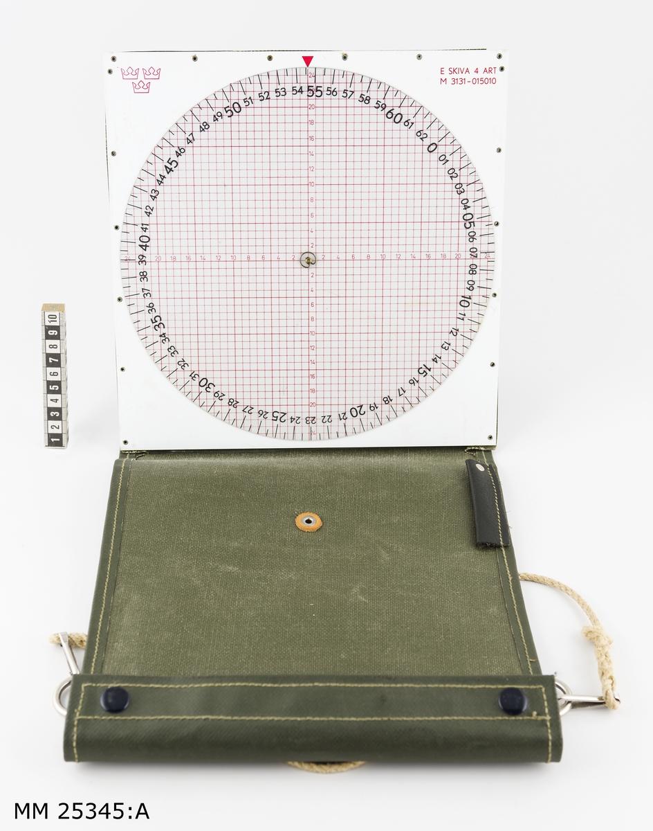 """På en vit kvadratisk plastskiva sitter en rund vridbar skiva som i stort täcker den underliggande skivan. På den underliggande skivan finns ett kors med streckangivelser från centrum och ut till mitten på de fyra sidorna. På skivan finns gradering i streck från 0 till 6 300. Märkt i övre vänstra hörnet med röd kronstämpel. I övre högra hörnet text: """"E SKIVA 4 ART M 3131-015010"""".  E skivan sitter fast monterad i ett grönt plastskydd som kan vika upp i ena änden. Under skivan en ficka för instruktionsböcker med mera. I plastfickan sitter ett snöre med två hakar i två av fyra ringar som är placerade på baksidan."""