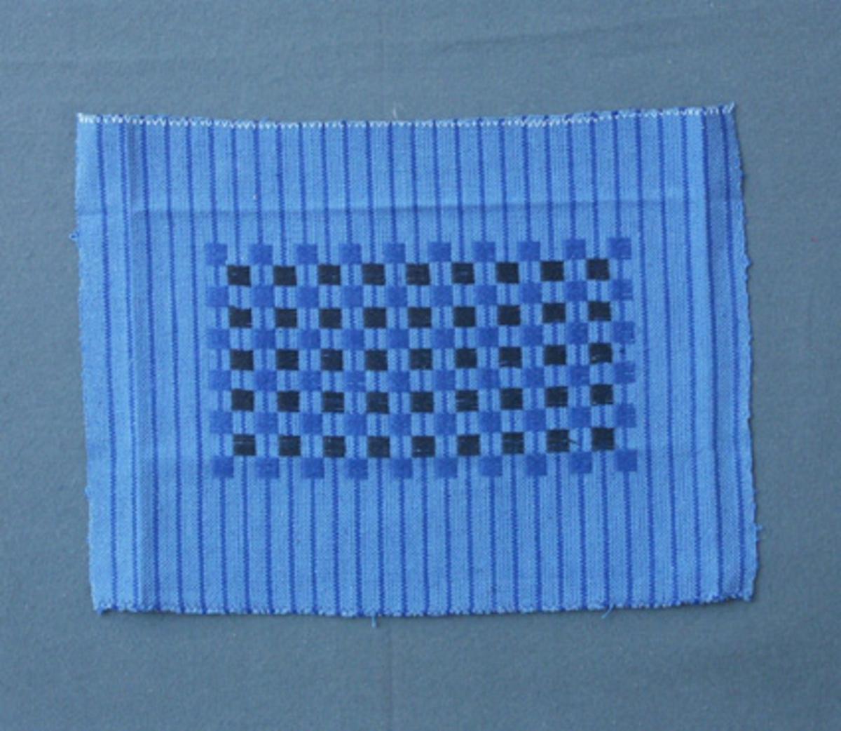Prov till kudde vävt i tuskaft med mönster i plattväv, eller tärningsväv som det kallats i  i tidigare inventering.