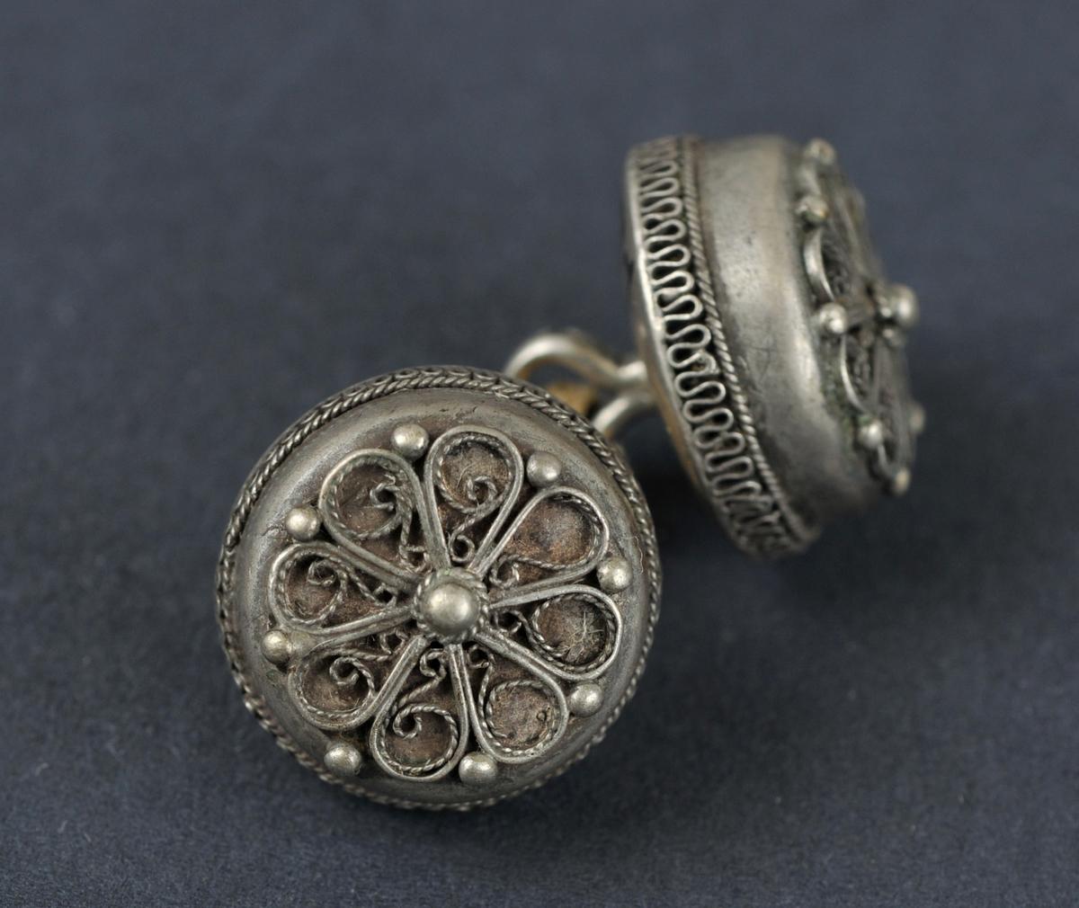 To knappar sett saman med bomullstråd. Flate på toppen med ein rosett m/8 blad i tvunnen sylvtråd. 8 små knuppar langs kanten og ein større på midten.