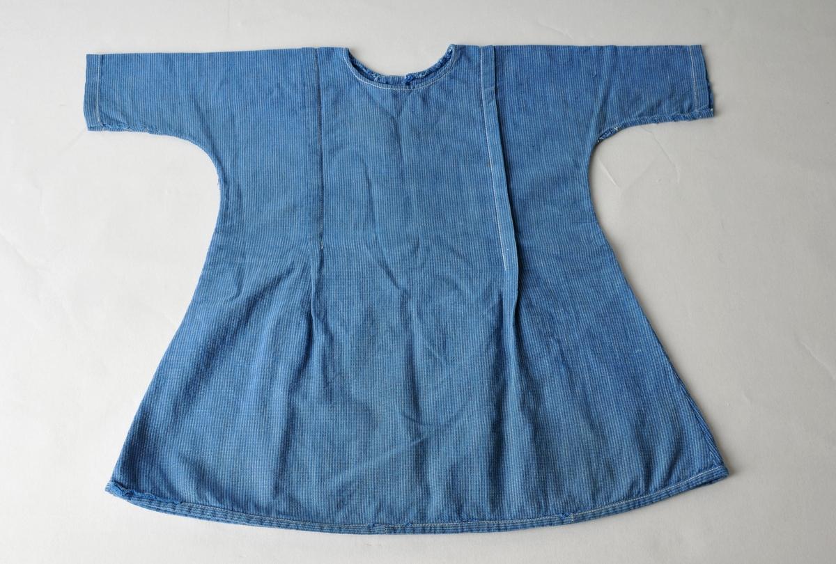"""Heimesydd barnekjole i blått bomullsstoff, """"blåtøy"""". Klipt i eitt stykke, men det er innfelt små stoffbitar på den eine sida framme, antageleg er kjolen laga av eit omsydd plagg. To legg foran og to bak, frå skuldera og ned til livet. Opning med knappestolpe foran. Storleik ca 2 år."""