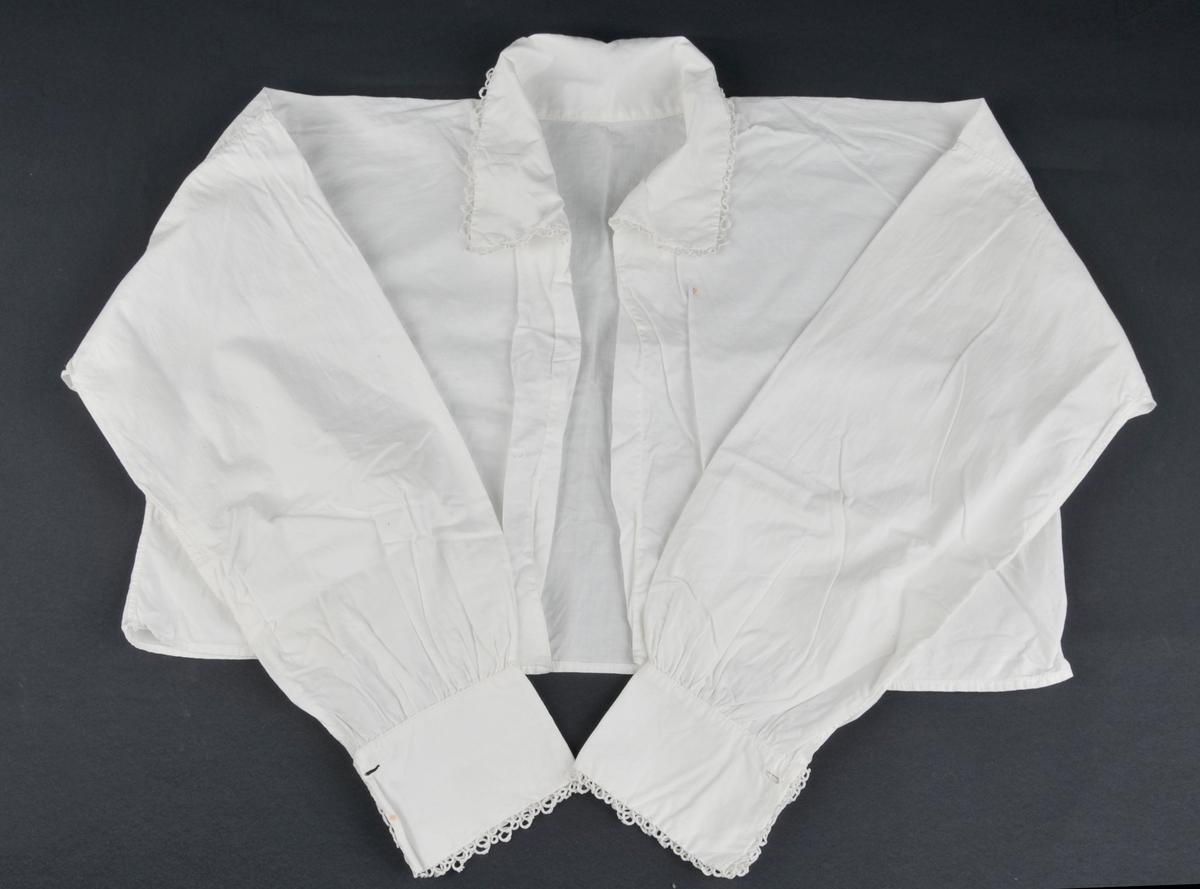 Skjorte, open framme. Enkle kniplingar på hals- og armliner. Primærsnitt.