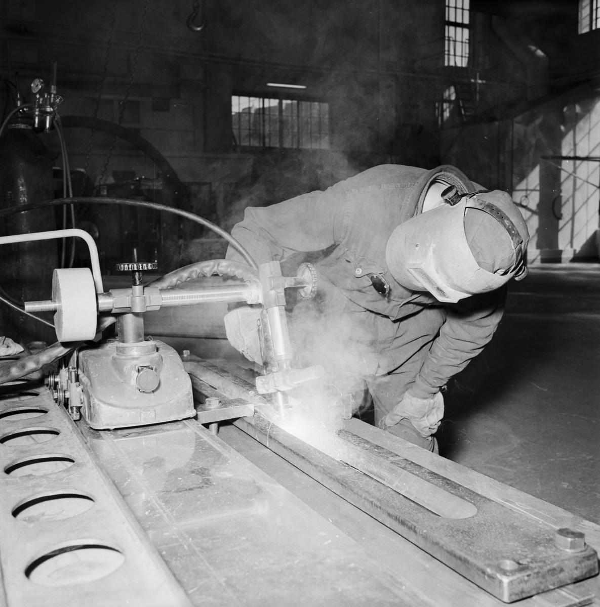 Övrigt: Foto datum: 16/3 1964 Verkstäder och personal. Bilder till reklambroschyr (Myllenberg) svetsning, dykare i arbete plåtpressen. Närmast identisk bild: V28530 och V28531, ej skannade