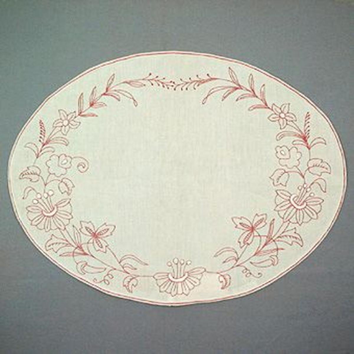 """Broderad brickduk i rosa och vitt bomullsgarn på halvblekt linne. Duken är märkt med en pappersetikett från Kronobergs läns Hemslöjdsförening i Växjö med handskriven text: """"163  """"AGNES"""" EFTER GAMMAL FÖRLAGA  Storl. 48 x 64  Matr. Pris: 185:- """"."""