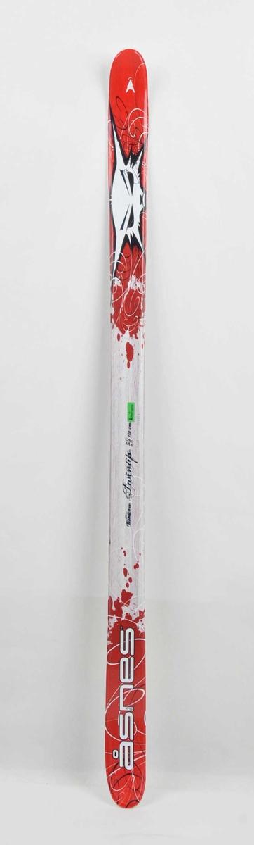 Barneski med tupp i begge endar, innsvinga mitt på. Fleire fargar og motiv oppe på skiet.