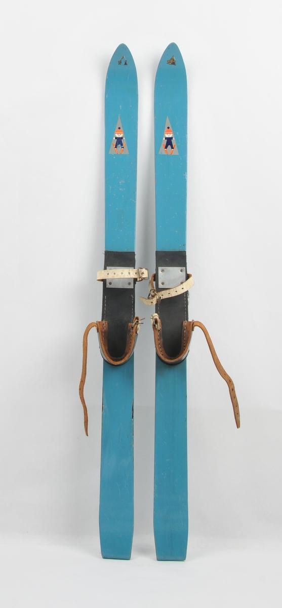 Langrennski for barn laga av tre. Emblem i framtupp og barnefigur på ski litt lengre ned. Lærsåle med hælfeste slik at ein kan spenne fast vanlege støvlar. Bruksslitasje.