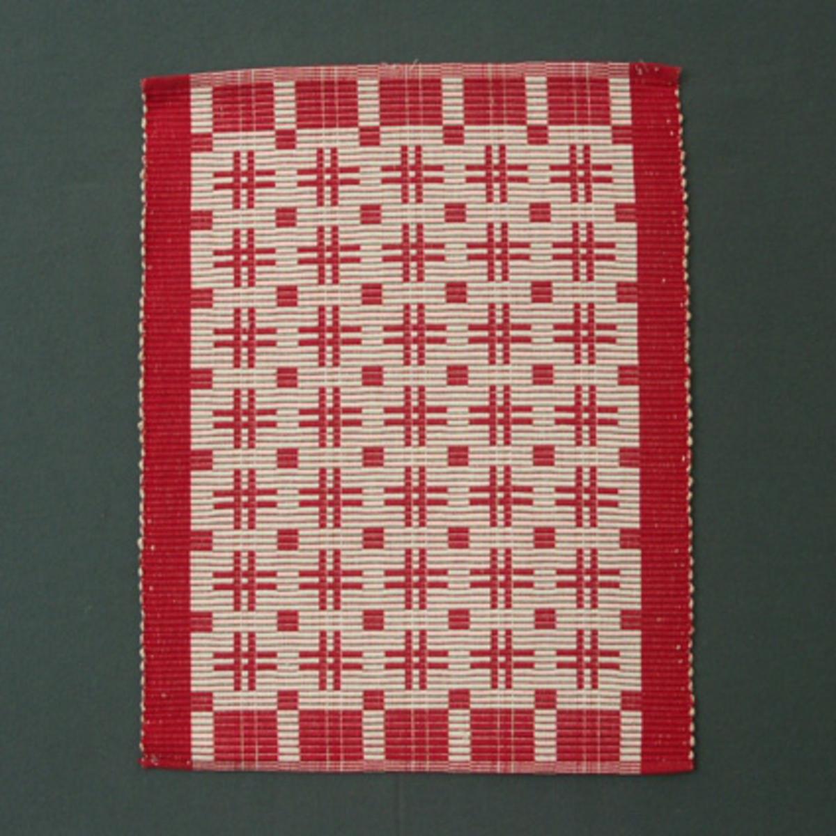 Tablett i rött och vitt vävd i varprips. Vävsedel finns i pärm nr 201 Rips, sida 9.