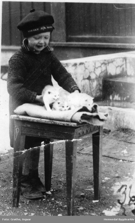 Johnny Grøthe steller ut kattungar utanfor barndomsheimen sin, Fagerheim, 67.37, i Hemsedal i 1936