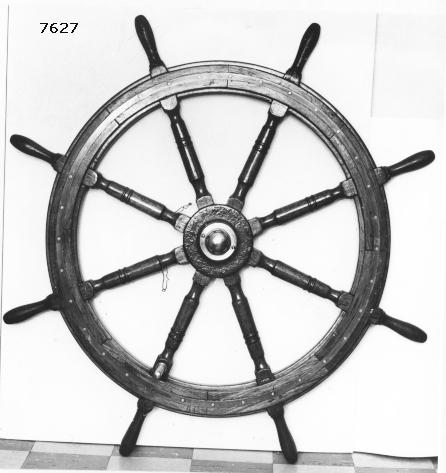 Drill, styrratt av ek, mässing och järn, gjuten. Rattens centrum av järn med runt hål och kilspår för styraxeln. Över hålet kåpa av mässing. Från centrum utgår åtta ekrar av trä genom hjulet. På ytterperiferin handtag. På ena ekern genomgående rund rattpinne av mässing,  Hjulet är på båda sidor förstärkt med skenor av mässing.