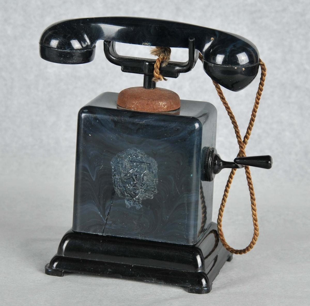 Svart telefon med sveiv. Riksløva i front. Røyret er festa til gaffelen med tvinna silketråd.