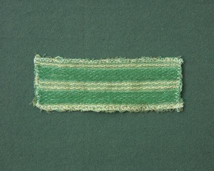 Randigt möbeltygsprov i grönt och oblekt vävt i korskypert och tuskaft med bomullsgarn i varp och lin- och bomullsgarn i inslag. Ytterligare prov och vissa vävuppgifter finns i pärm Möbeltyg a, litt c 210.