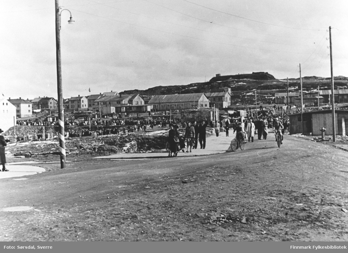 Vardø 17. mai ca 1948. Det er masse folk ute. Noen sykler i forgrunnen. Det er trebrakker og trehus i bakgrunnen.