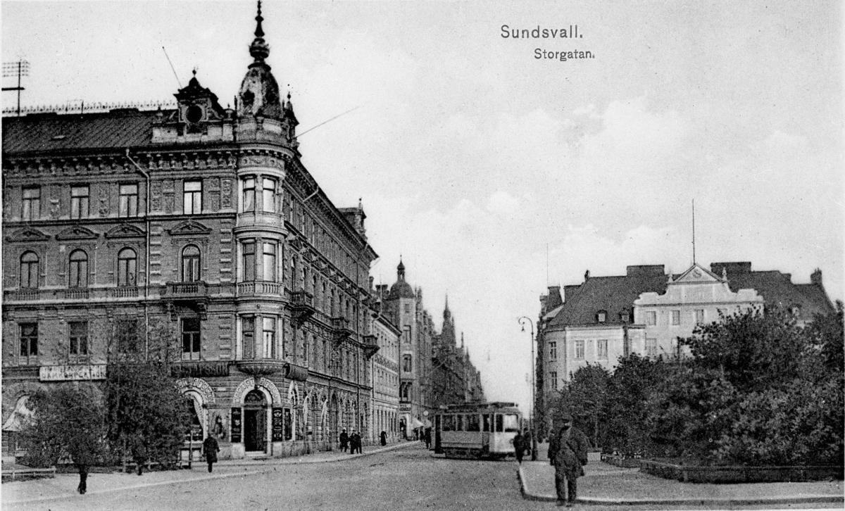 """Från vänster kv Olympen 3-4/Kihlmanska huset, kv Jupiter 4 till höger i bild kv Proserpina 1/Sundsvalls handelsbank, kv Vängåvan/Park. På Storgatan spårvagn och fotgängare. Text till bild """"Storgatan. Sundsvall. På kv Olympen syns på bilden text """"C A GUSTAFSSON"""", """" WINHANDEL"""", """"SYDFRUKTER"""", """"DELIKATESSER""""."""
