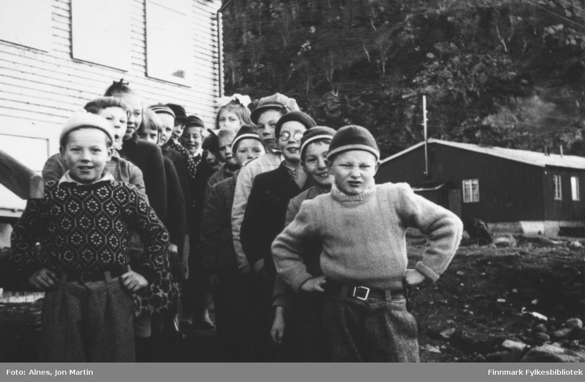 Klassebilde av 4. klasse ved Øksfjord barneskole 1953. I bakgrunnen ser vi bygninga som ble brukt til skolebrakke før den nye skolen kom. Ble også brukt som skoleinternat