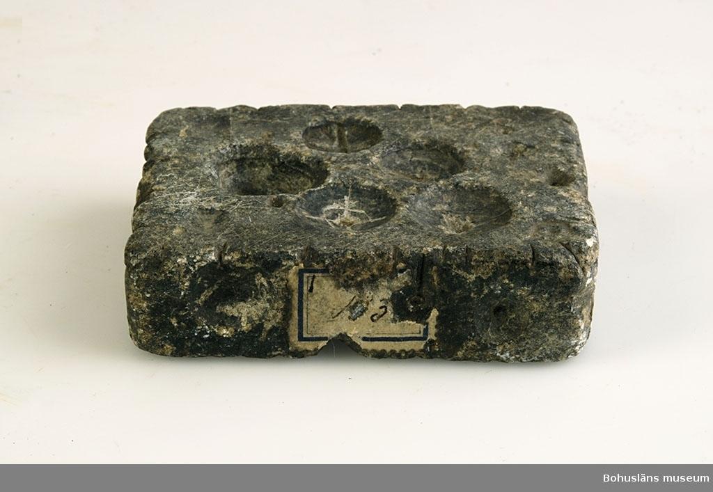 Ur handskrivna katalogen 1957-1958: Knappform av täljsten Mått: 8,5 x 6,5 x 2,2 cm; för 17 knappar. Föremålet helt.