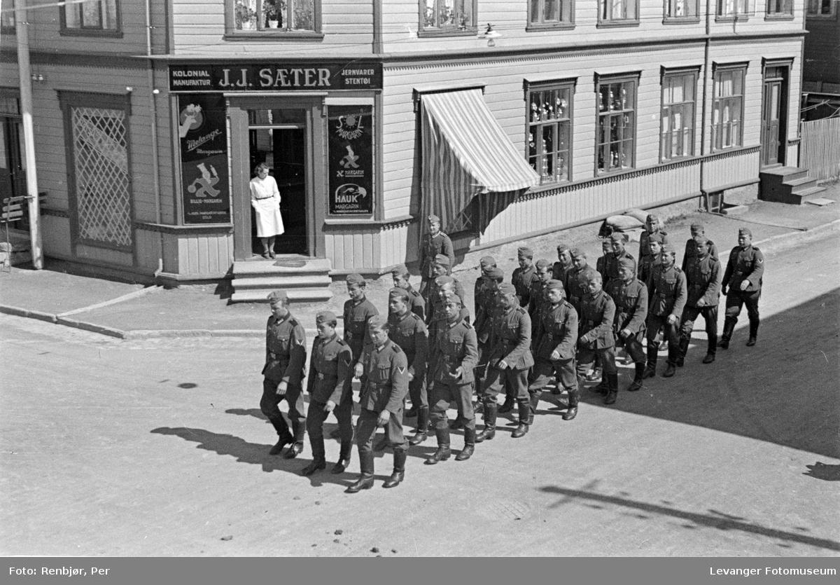Gatescene tatt fra 2 etasje fra vundu, tyske tropper marsjerer mens en kvinne observerer fra butikken til Sæter.