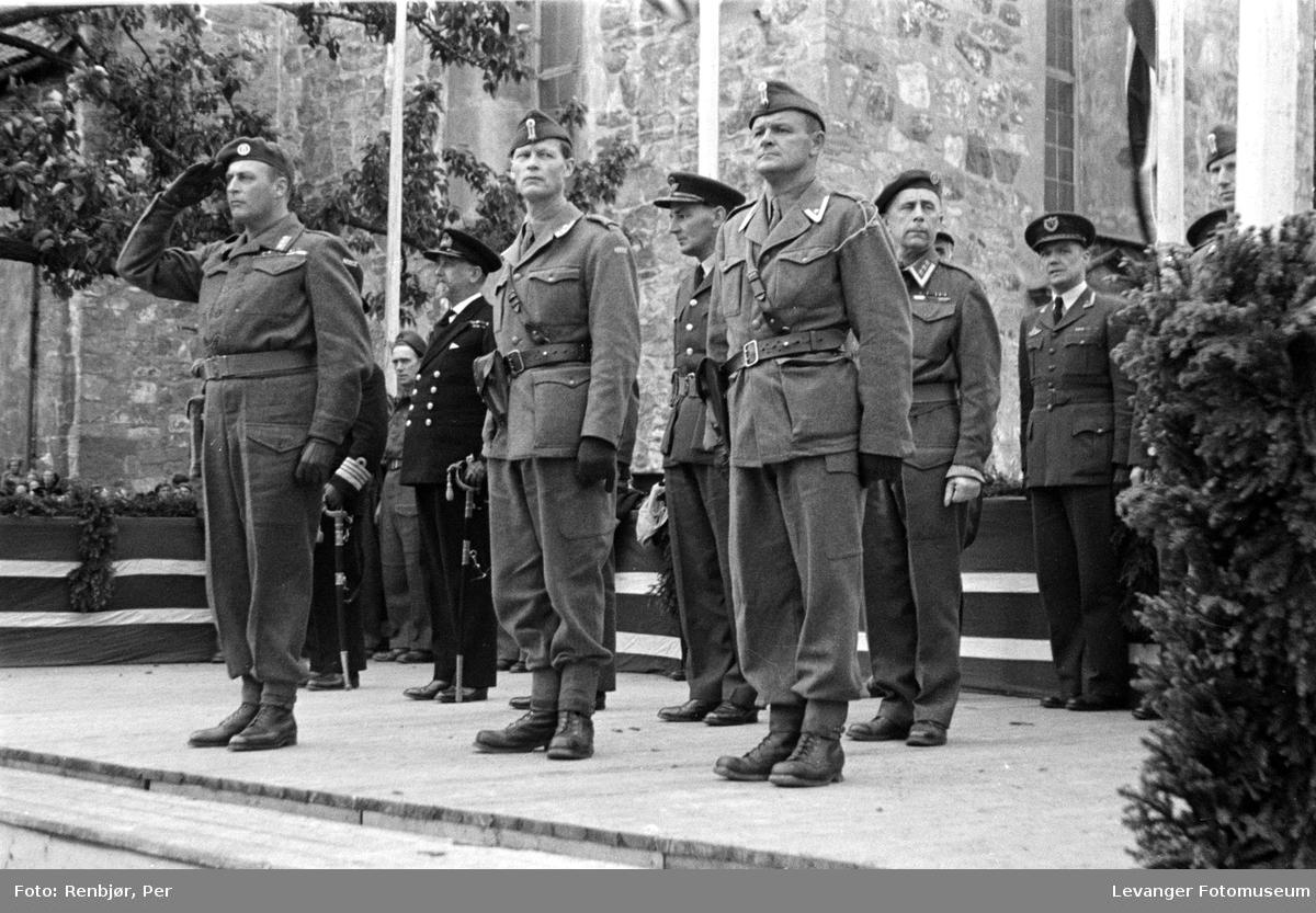 Kronprinsen salutterer soldatene på tribunen. med offiserer fra ulike våpengrener.