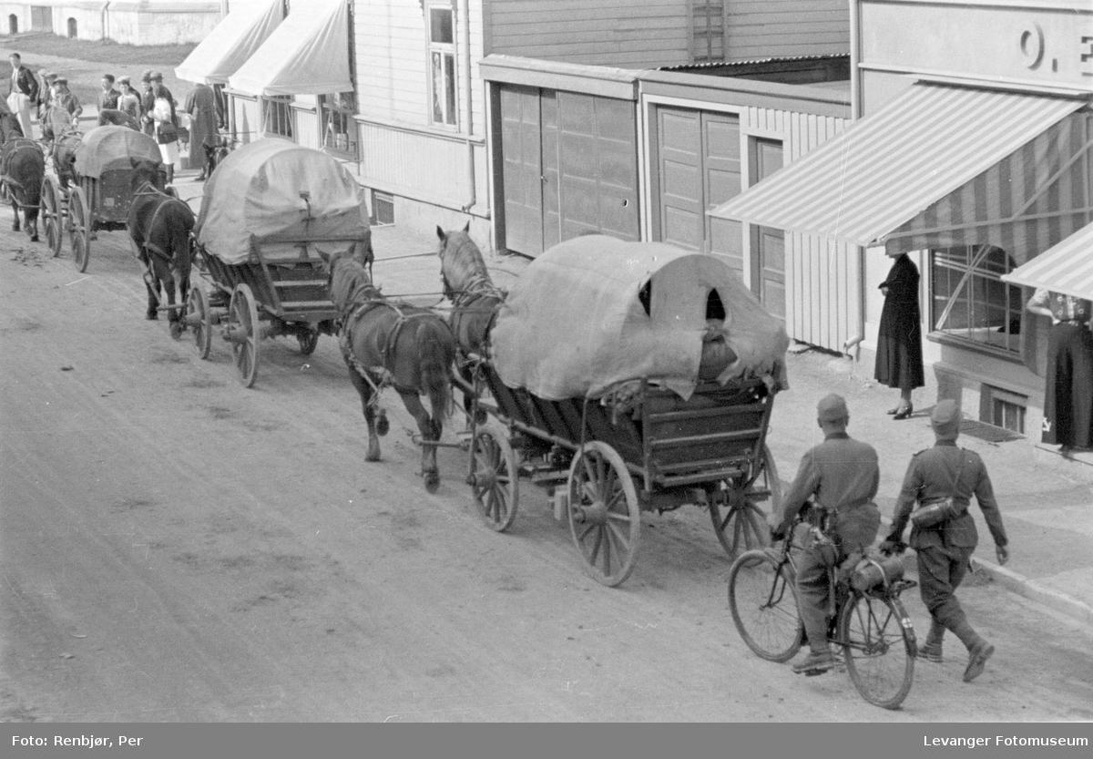 Tysk kolonne med hester og syklende soldat på veg opp gata.