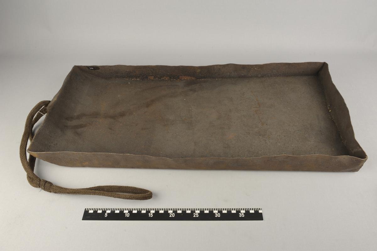 Metallkasse. I den ene kortenden er kanten skrånende, og det er et hull midt på denne siden. I hullet er det festet et tau. Kassen er rustet.