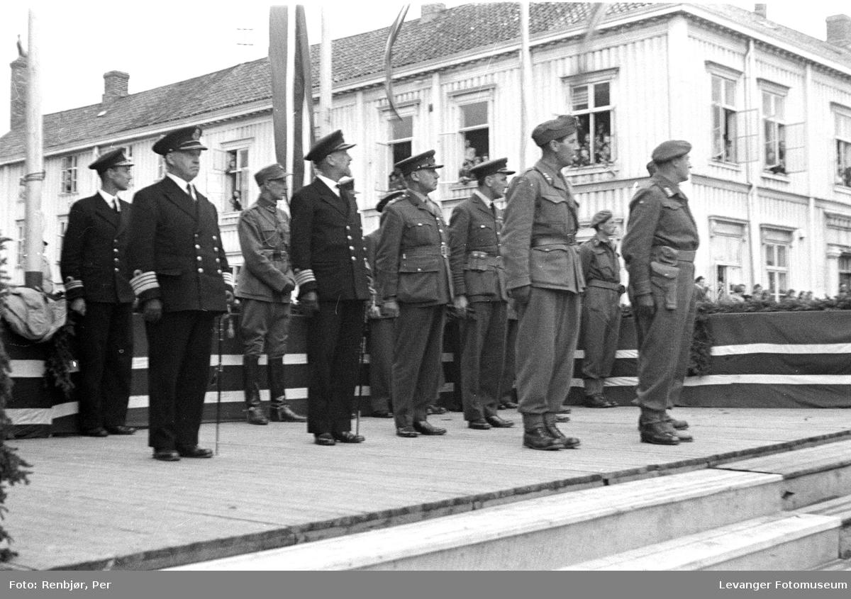 Høyerer norske offiserer fra ulike våpengrener med kronprins Olav på Ærestribunen foran Hornemannsgården.