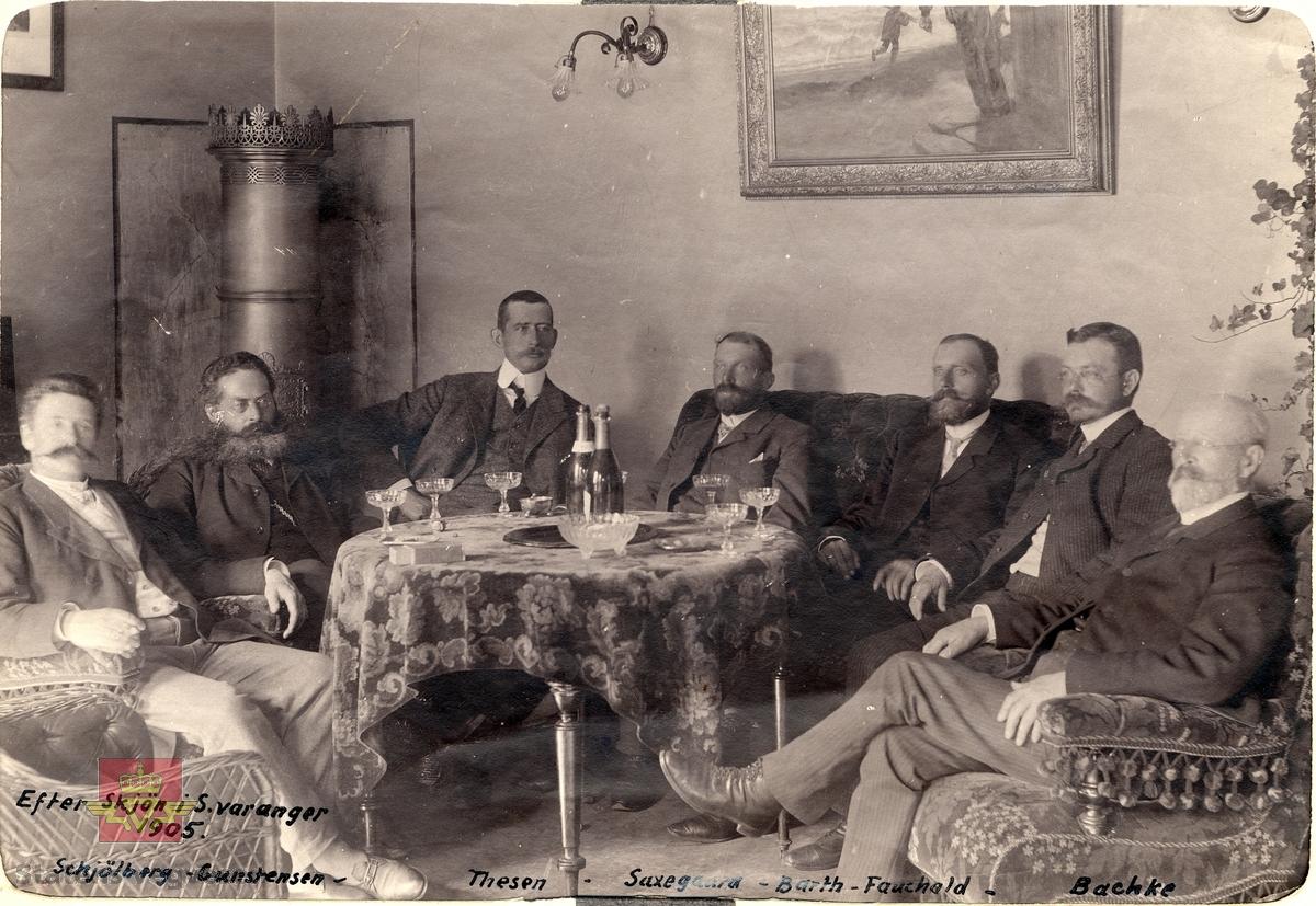 """Tekst påskrevet på bilde: """" Efter skjøn i S. Varanger 1905. Schjölberg-Gunstensen-Thesen-Saxegaard-Barth-Fauchald-Bachke"""". Bilde av en gruppe menn, blant annet av amtsingeniør Saxegaard på midten av bildet.  I hjørnet står en sylinderformet koks/kull ovn. Champagneglass på mønstret velour duk på bordet. Mønstret møbler i klunkestil og rottingstoler. Bildet er en del av Saxegaards album, se historikk.  08.01.2018: """"Mannen som sitter helt til høyre på bildet er Anton Sofus Bachke"""". Opplysning fra  Anne Mette Gottschal."""
