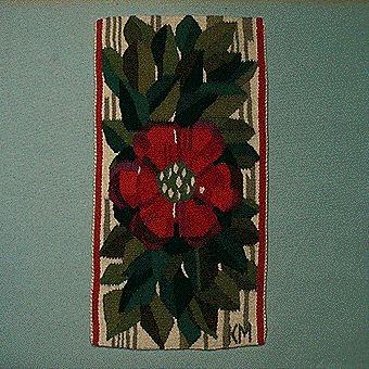 """Bildväv i flamskteknik med motiv av en stor, enkel blomma med röd-lila kronblad i en buske av olika gröna nyanser. Bakgrunden är grovt randad i vitt och grått. Varp av lintråd, inplock av ullgarn. Monterad med langettkant och orientalisk fläta. Fastsydd klisterlapp på baksidan med texten; """"Höstaster"""". Jämför med inv.nr 1045."""